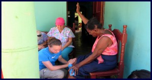 Cori praying for Dominican woman in Brisas del Mar